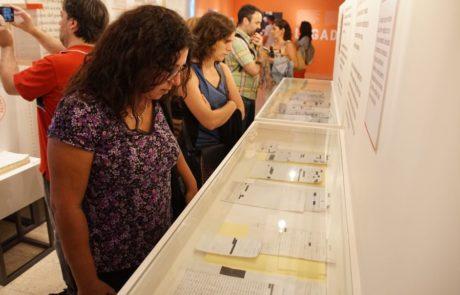 Visitantes observan las vitrinas con documentos clasificados que forman parte de la muestra